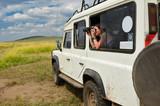 Woman tourist on safari in Africa, travel in Kenya, watching wildlife in savanna with binoculars  - 133329732