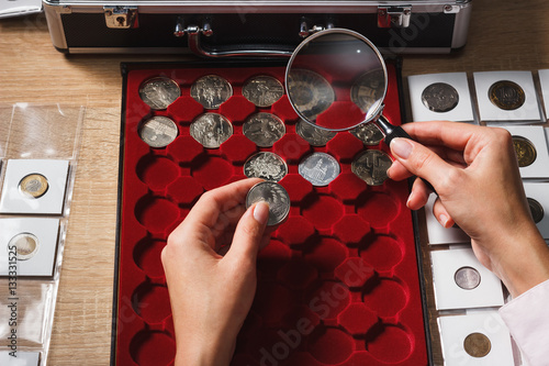Zdjęcia Woman looks at the coin through a magnifying glass