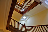 Brown wood staircase with a handrail in a building without an elevator