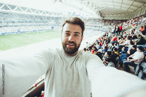 Handsome bearded supporter watching football game and making selfie self-portrait with smartphone at Camp Nou, Barcelona, Spain