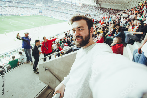 Poster Handsome bearded supporter watching football game and making selfie self-portrait with smartphone at Camp Nou, Barcelona, Spain
