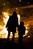 Silueta de una madre e hijo junto a un gran fuego