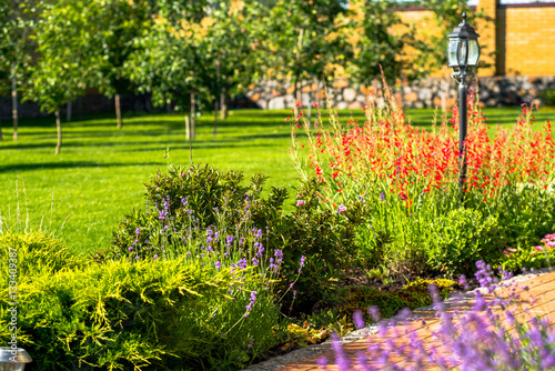In de dag Lime groen Beautiful backyard landscape design. View of colorful trees and decorative trimmed bushes and rocks