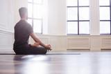 Fototapety Young men do yoga indoors on black mat