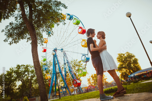 Poster guy and the girl hugging at amusement background
