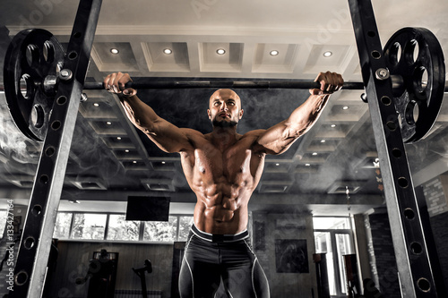 Poster Bald Bodybuilder preparing for exercise with barbell in gym