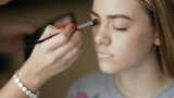 Master doing makeup for model