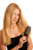 Beautiful blonde woman brushing her hair as a sign og hair care