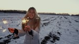 Cute woman dancing and smiling with light sparklers in the winter field. Slow motion 120 fps Concept: Fun, Freedom, Celebration, Joy, lifestyle