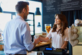 Young female barista serving coffee to customer in cafe - 133435766