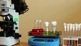 Laboratory workspace overview by panning. Camera moves to right – from microscope, rotating shaker with glassware to colorful agar microbiological tubes. Focus on full depth.