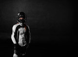 Fototapety Young handsome woman model in motorcycle concept. Extreme girl in bike helmet and motor protection race suit on black background with free space for advertising or goods.