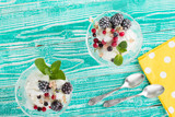 sherbet glass with ice cream decorated by mint leaf and frozen berries on  turquoise colored wooden background, silver tea spoon, yellow napkin at white polka dots pattern,  top view, - 133473790