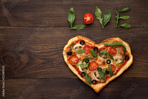 Foto op Canvas Pizzeria Heart shaped pizza for Valentines day on dark rustic wooden background with text love.