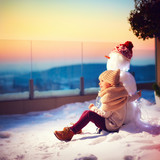 happy little kid and his friend snowman watching the sun goes down sitting in snow on rooftop terrace in one winter evening