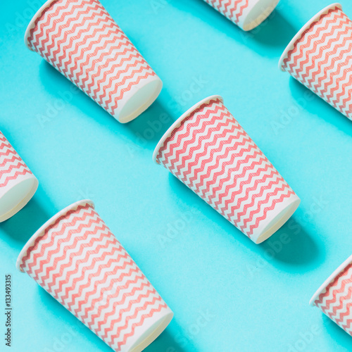 Poster Paper cups by pink color lined diagonally on the mint background
