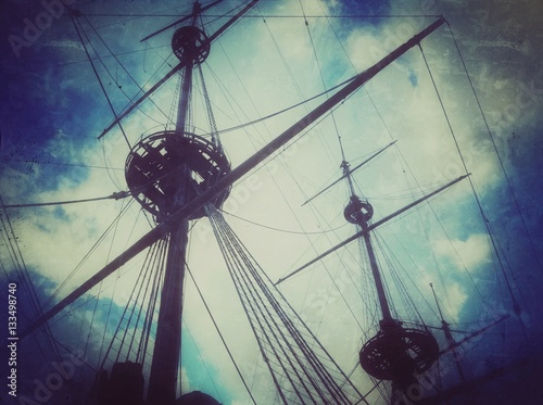 Fotobehang Schip Old vintage ship masts photo with scratches and damages antique blue texture.