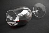 Copa de vino tinto tumbada sobre fondo negro