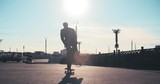 ear view of businessman with briefcase skateboarding on the street at sunny summer day