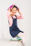 Smiling schoolgirl sitting on books