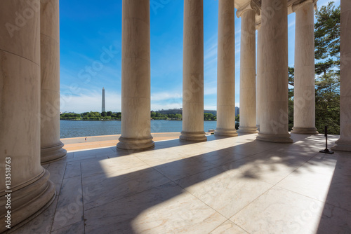 Columns at the Jefferson Memorial and the Washington monument on the horizon in Washington DC Poster