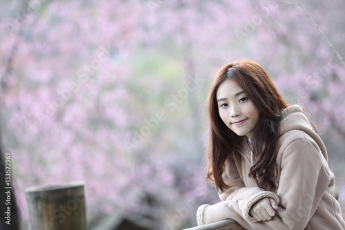 Poster beautiful asian young woman in blooming cherry blossoms sakura