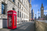 London, England - Traditional red british telephone box with Big Ben and Double Decker bus at the background on a sunny afternoon with blue sky and clouds - 133527148