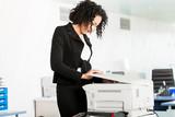 Geschäftsfrau steht am Kopierer