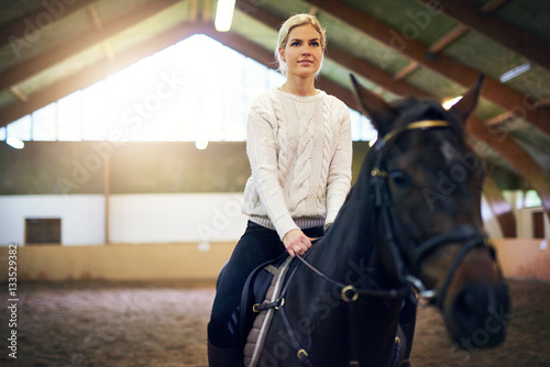 Female sitting astride in indoor riding hall Poster