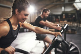 Fototapety Two young people training on cycling machines