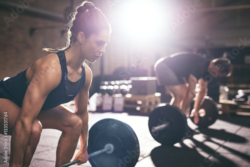 Wall mural Muscular man and woman lifting heavy barbells