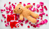 Funny picture of teddy bear naked on roses. Valentine background.