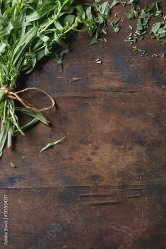 Bundle of fresh and cutting Italian herbs rosemary, oregano and sage over old dark wooden background. Top view with copy space