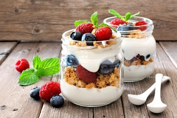 Blueberry and raspberry parfaits in mason jars, still life against a rustic wood background