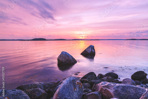 Plexiglas Lichtroze Violet toning sea shore landscape with great stones at foreground. Location: Sweden, Europe.