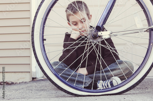 Poster Sad boy looking at his flat bike tire