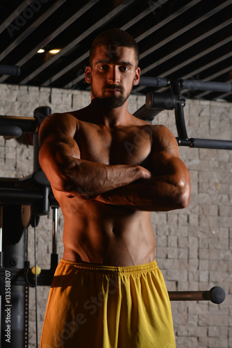 Poster Serious Young Bodybuilder Standing In The Gym
