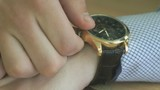 The man checks the time of the wristwatch. Close up