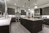 Modern gray kitchen features dark gray flat front cabinets paired with white quartz countertops and a glossy gray linear tile backsplash. Northwest, USA. - 133612557