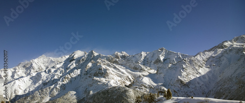Aerial Views of an Alpine Valley and High Mountains covered in Fresh Snow