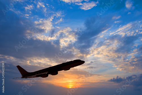 Poster Silhouette of an airplane taking off, sunset background