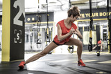 Fototapety Athletic girl does stretching in gym