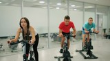 Young people prepares to the exercise on the exercise bike in the gym