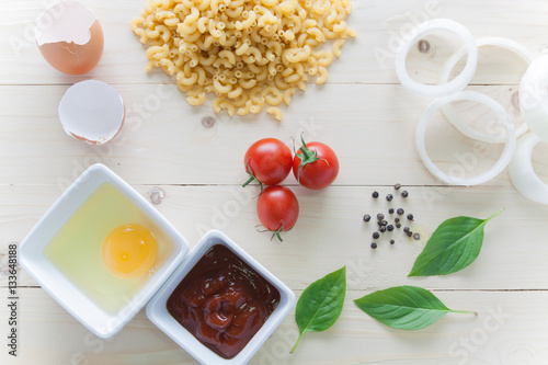 Poster spaghetti with ingredients for cooking on wood background