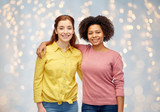 happy smiling women hugging over holidays lights