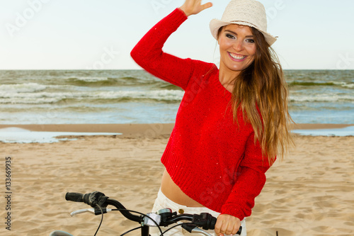 Poster Beauty tourist with bike on beach.