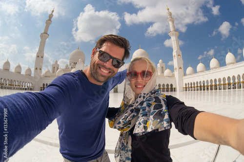 Foto op Canvas Abu Dhabi Tourist couple taking selfie in the courtyard of famous Sheikh Zayed Grand Mosque in Abu Dhabi, United Arab Emirates.