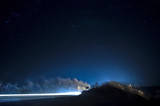 Beautiful stars on night sky near road with car light tracks