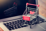 Tablet and shopping cart on wood table, Online shopping concept