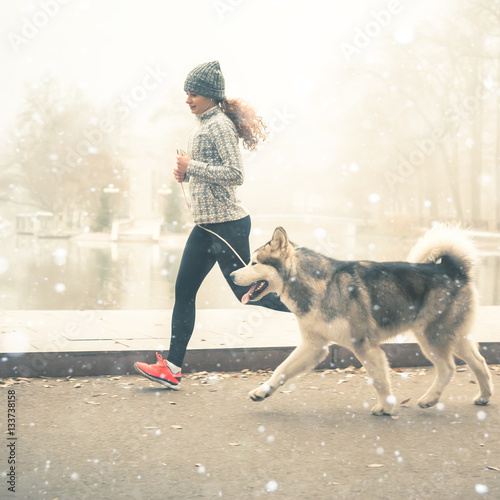 Poster Image of young girl running with her dog, alaskan malamute